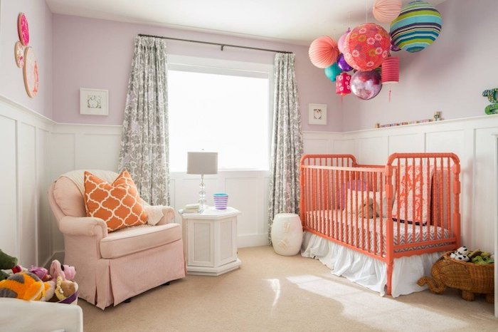 lots of multicolored paper lanterns, with different colors, shapes and sizes, hanging over orange baby crib, nursery ideas, pale orange armchair