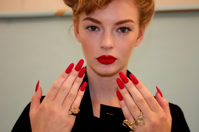 blonde woman with hair tied up, dressed in black, and holding up her hands, with long oval red manicure, and lipstick in matching color