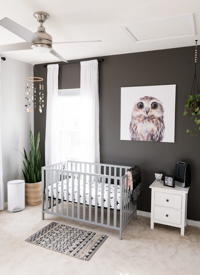 dark brown and white walls, light gray crib with white bedding, gender neutral nursery, painting of adorable owl, light beige floor