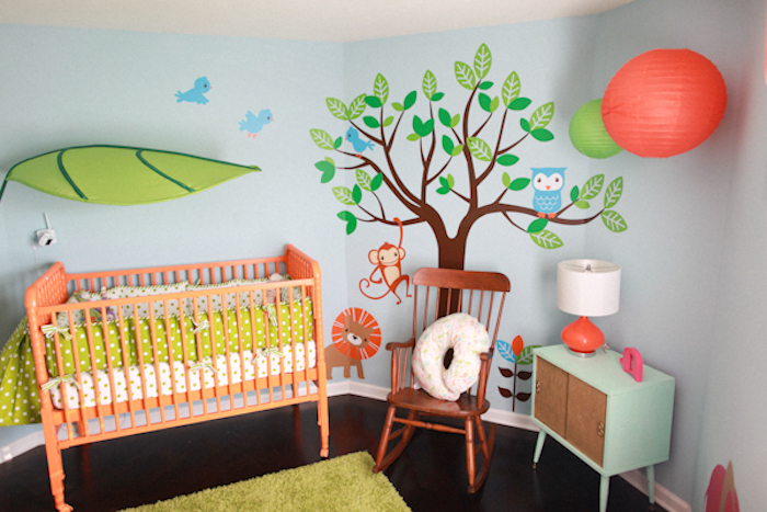 decal with a cartoon tree, birds and animals, on pale blue wall, near light turquoise cupboard, baby girl room décor, orange crib with light green bedding, and vintage rocking chair