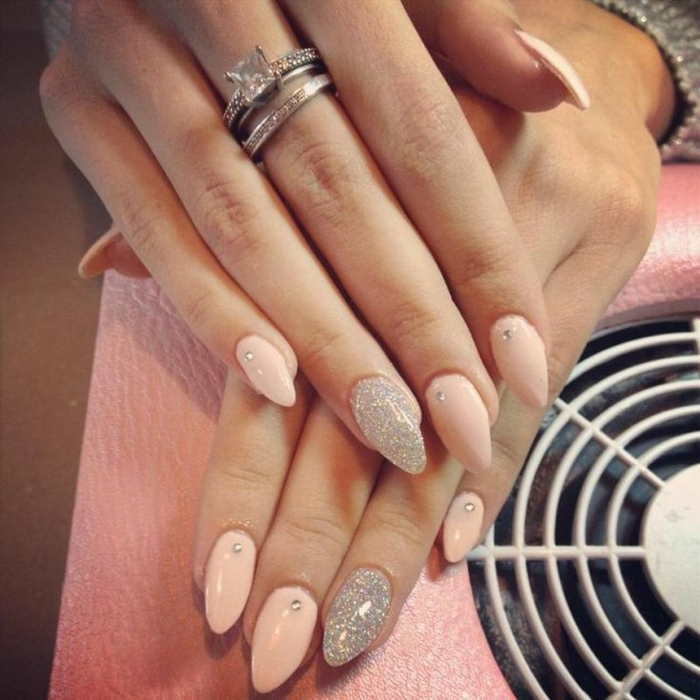 milky pastel pink, stiletto acrylic nails, decorated with small rhinestone stickers, and silver glitter