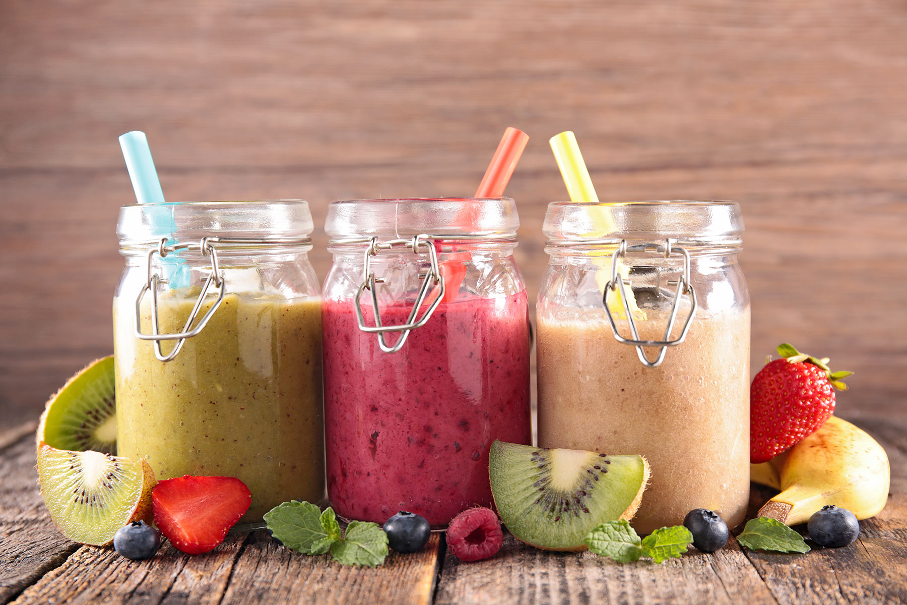 slices of kiwi and strawberry, blueberries and mint, near three jars with snap lids, containing blended drinks in different colors, healthy smoothie recipes, straws and a banana