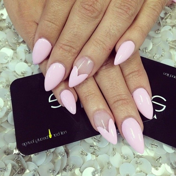 short stiletto nails, sharp and painted in pale, pastel pink nail polish, with heart details