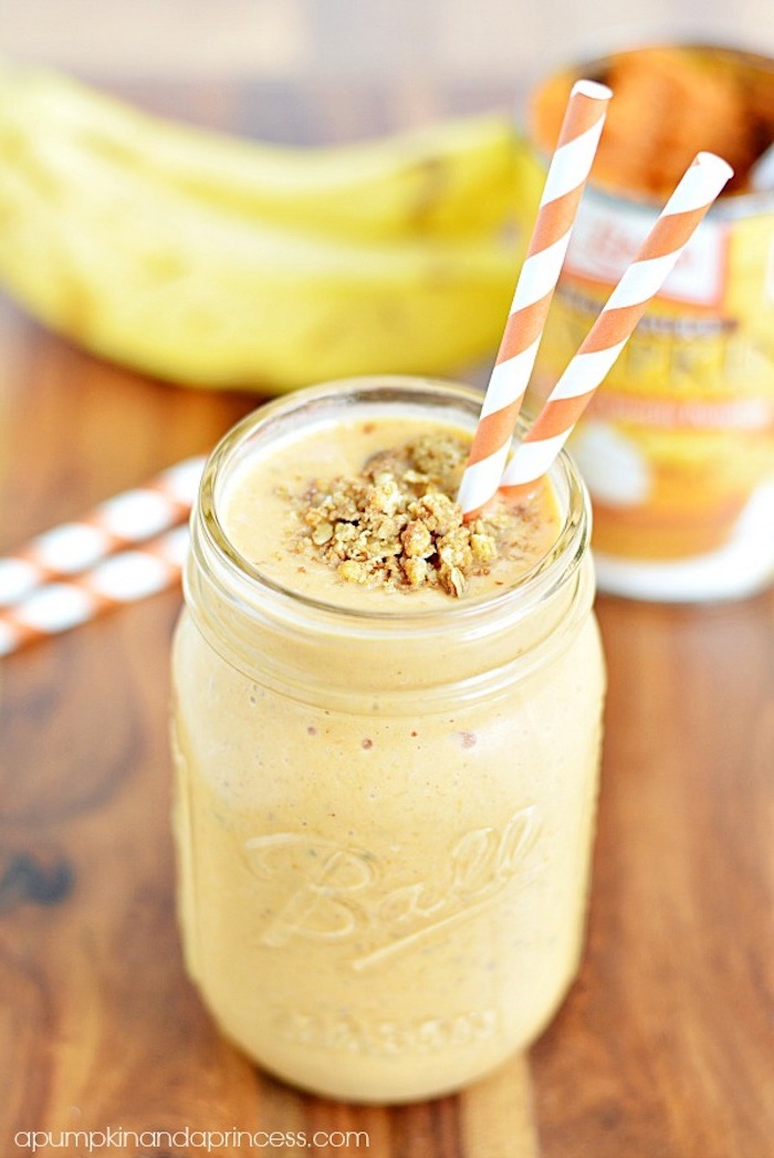 striped paper straws in white and orange, inside a ball jar, filled with creamy pale orange drink, topped with crushed nuts, easy smoothie recipes, bananas in background