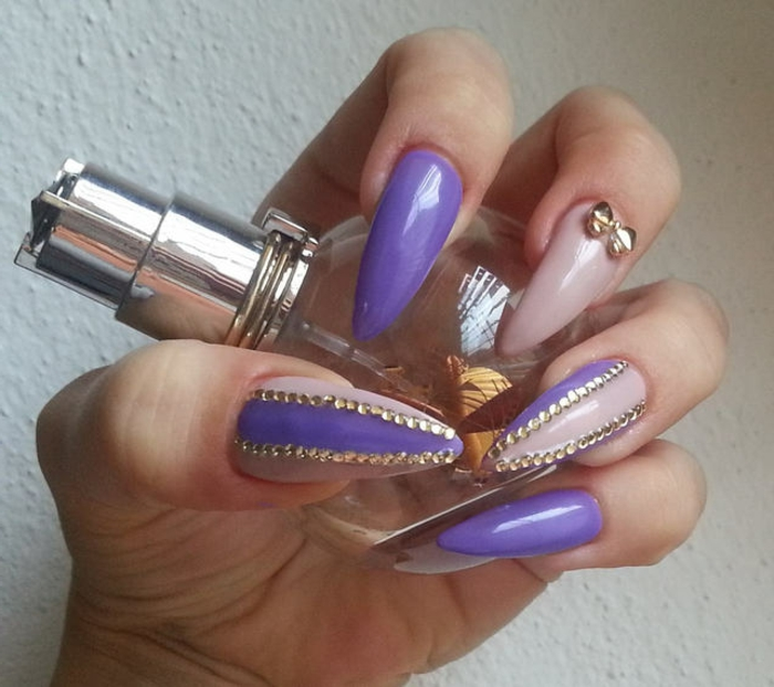 kitsch-style claw nails, in violet and light pink, decorated with lots of tiny, round golden rhinestone stickers, and a single golden bow shape, on hand-holding a perfume bottle