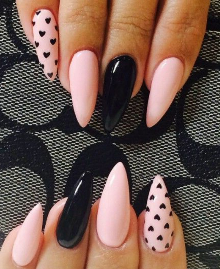 pale pink and black stiletto nails, some decorated with small, hand-drawn hearts print, others left plain