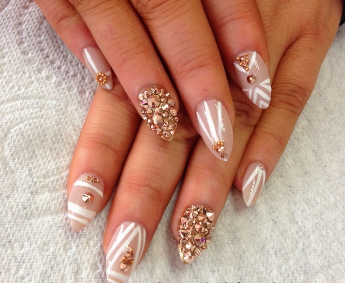 rose gold rhinestone nail decals, on beige-pink colored sharp nails, decorated with white stripes