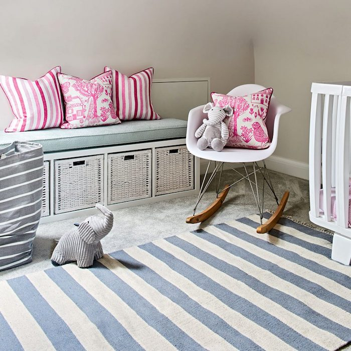 four vibrant pink and white cushions, placed on storage bench, and small white rocking chair, baby girl room décor, striped rug in cream and blue, stuffed elephant toy