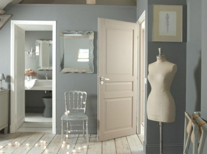 mirror and vintage chair, walls with blue grey paint, white door looking inside a bathroom, light wooden floor, fairy-lights and a dressmaker's dummy