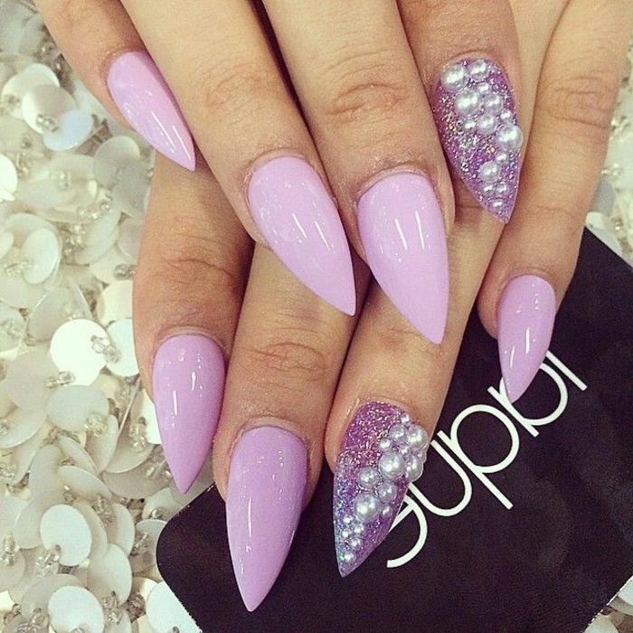 light pastel violet nail polish, smooth and shiny, with silver pearl-stickers, and violet glitter, on stiletto acrylic nails