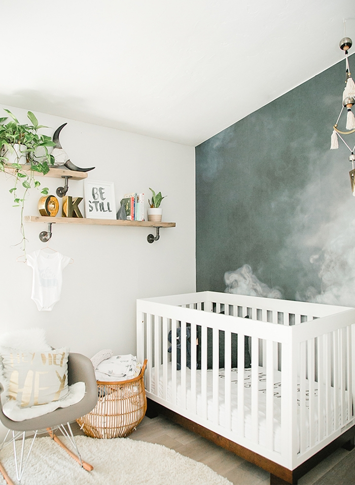 dark bluish-gray mural with white clouds, two wooden shelves, with potted plants, white wooden crib, and beige rocking chair, in gender neutral nursery