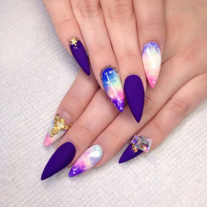 sunset sky-colored, long stiletto nails, with splashes of blue and pink, purple and white, matte purple manicure, decorative golden and iridescent stickers