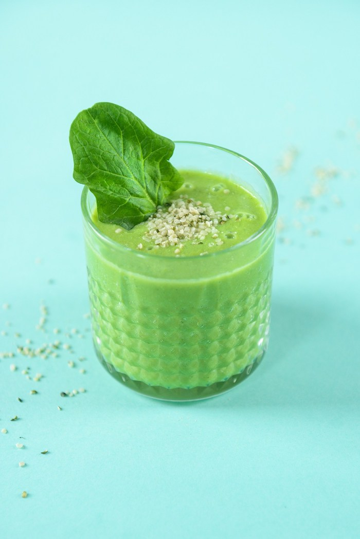 spinach smoothie, inside a small, crystal tumbler glass, with a textured pattern, topped with small seeds
