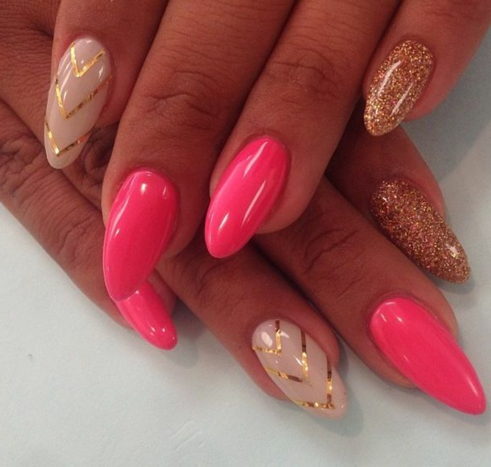 hot pink and beige nail polish, decorated with golden glitter and stripes, on oval pointy manicure