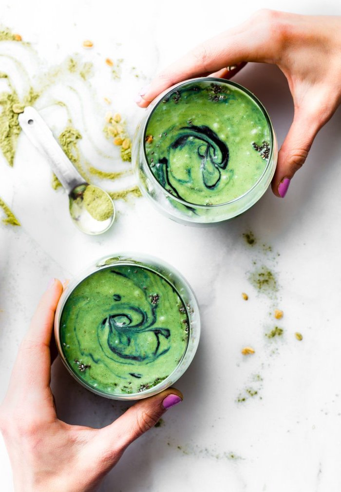 matcha powder in a green smoothie, poured into two glasses, each held by a hand, with pink nail polish, measuring spoon with matcha nearby