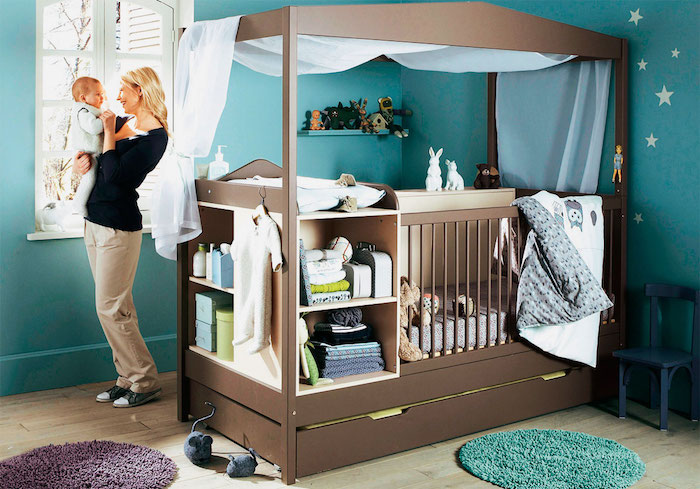 all-in-one baby crib, with changing table, storage space and shelves, made from brown wood, inside a boy nursery, with teal blue walls, blonde woman holding a baby