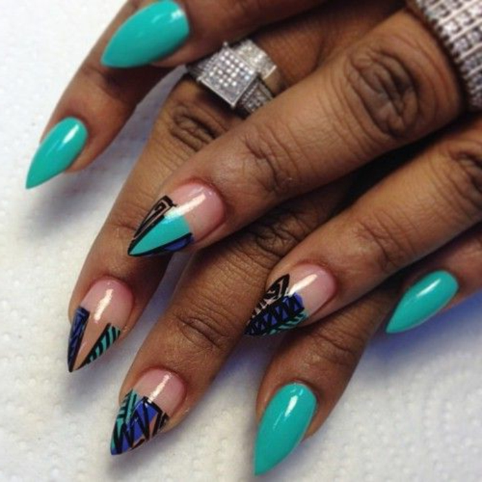 clear nail polish details, on short stiletto nails, painted in turquoise, and decorated with black, hand-drawn ornaments, and pink and blue stripes