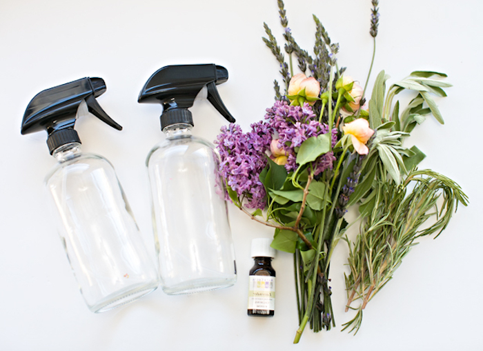 bouquet of flowers and herbs, near two empty clear bottles, with black plastic caps, mother's day gift ideas, and a small bottle of lavender essential oil