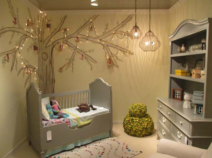 matching gray ornamental crib, and cupboard with shelves, in baby nursery, with pale yellow walls, and tree mural, decorated with tiny fairy lights