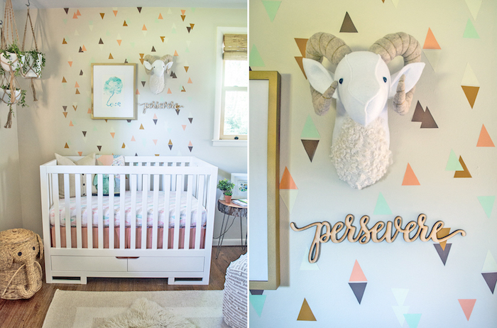 baby girl themes, pale off-white wall, decorated with triangle shapes, in natural colors, with white wooden crib, plush ram's head decoration, and hanging potted plants