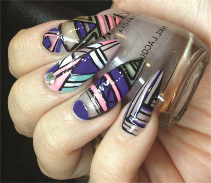 abstract shapes in dark violet, light pink, black and teal, with a single rhinestone sticker, on clear claw nails