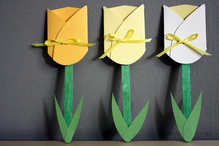 kid's crafts projects, mother's day gifts for grandma, three paper tulips, in yellow and white, with small ribbons, green paper leaves, and hand-colored stalks