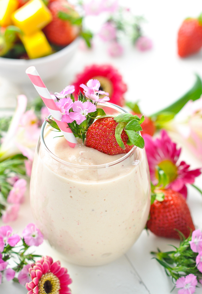 strawberry and small pink flowers, topping a tumbler glass, filled with pale pinkish-beige drink, protein shake recipes, more berries and flowers nearby