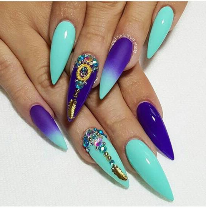 blue-green and purple claw nails, with ombre effect, various golden details, and many multicolored, gem-shaped nail decal stickers