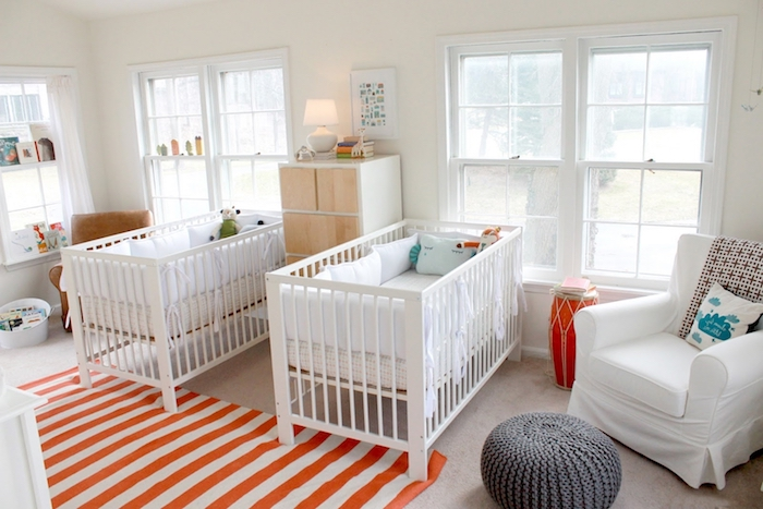 nursery ideas for twins, orange and white striped rug, pale beige carpet, two identical white, wooden cribs with cushions and toys