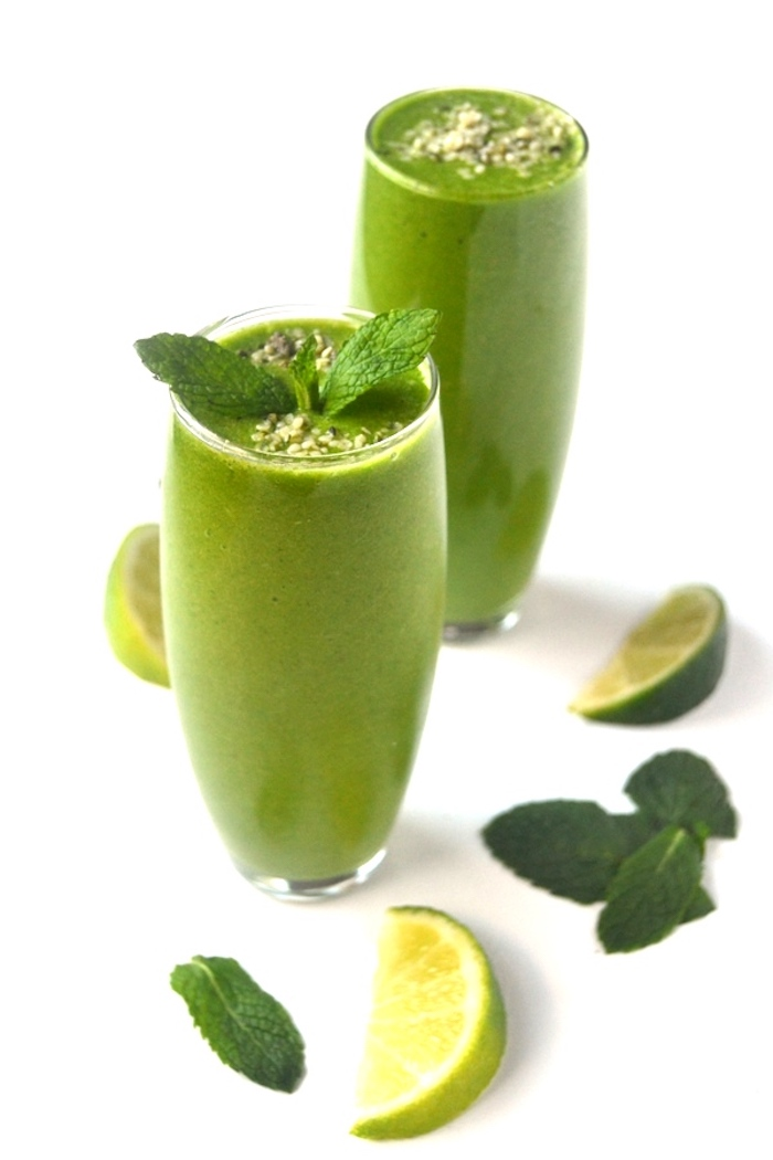 lime edges and mint leaves, near two tall glasses, filled with a green smoothie, each topped with small seeds