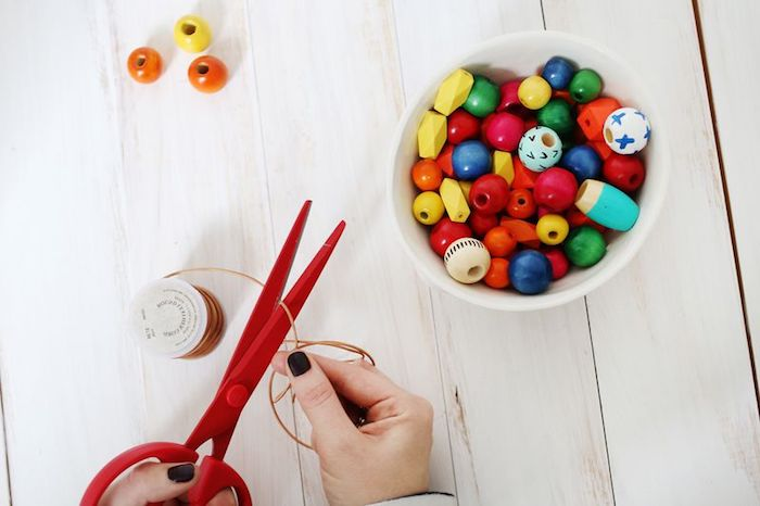 mother's day gift ideas, cutting leather cord, with pair of red scissors, white bowl filled with multicolored, wooden bead nearby