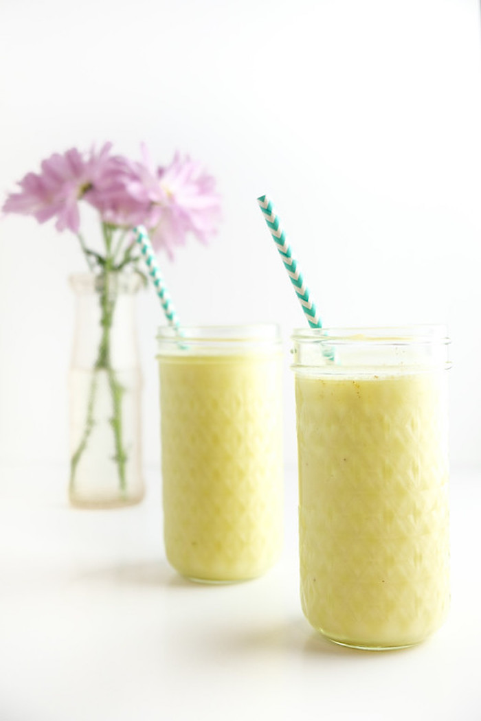 purple flowers in a clear vase, near two tall glasses, containing a pale yellow blended drink, healthy smoothie recipes, two striped straws