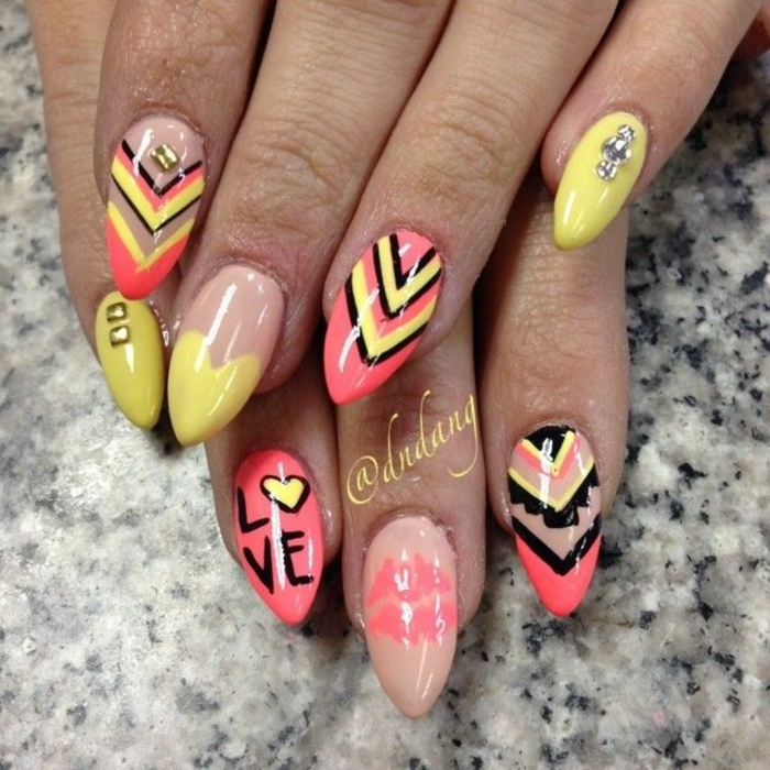 cheerful nails in yellow and beige, black and orange, decorated with different shapes, rhinestones and scribbles, stilleto nail designs