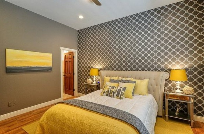 painting in yellow and gray, inside grey bedroom, with patterned wallpaper, pale beige bed, white and gray, and yellow bedding