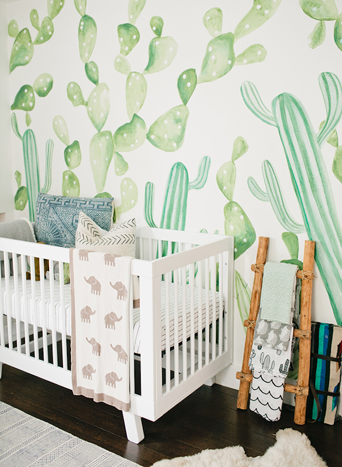 gender neutral nursery, watercolor effect wallpaper, with light green cacti pattern, white wooden baby crib, dark wooden floor, nature inspired room