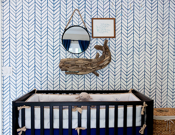 round wall mirror, near framed text, and wooden whale ornament, boys room ideas, black wooden crib, white and blue wallpaper