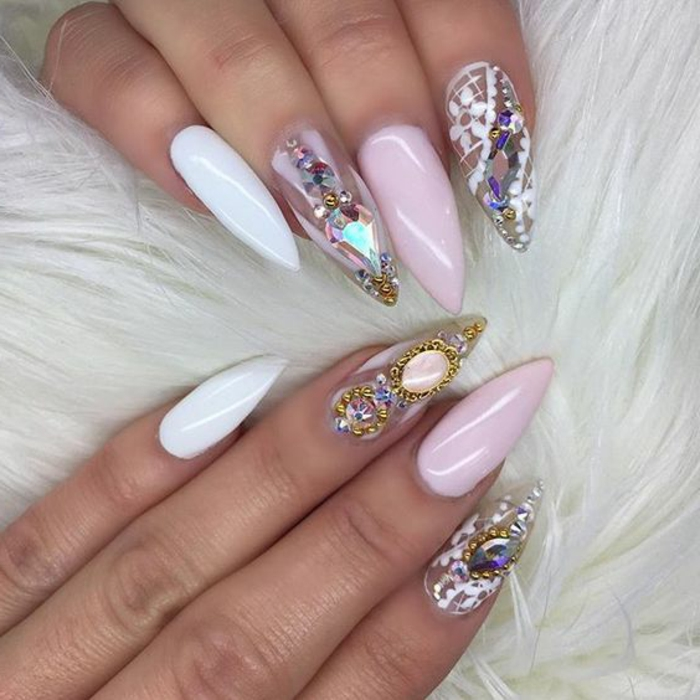 golden decorations and rhinestone stickers, on long pointy nails, painted in clear, white and pale pink nail polish