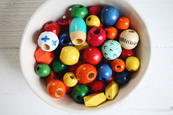 lots of wooden beads, in different shapes and sizes, inside a white ceramic bowl, mothers day gifts, necklace materials