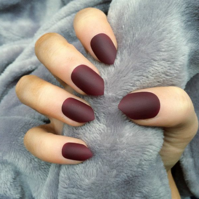 burgundy or deep red short stiletto nails, with sharp tips, on hand holding pale, grey plush blanket