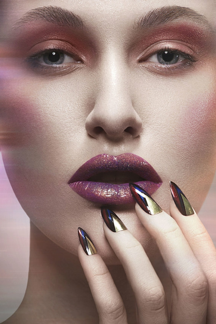 model with strong make-up, holding one hand to her face, with long manicure, stilleto nail designs, blue and black, red and gold metallic nail polish colors