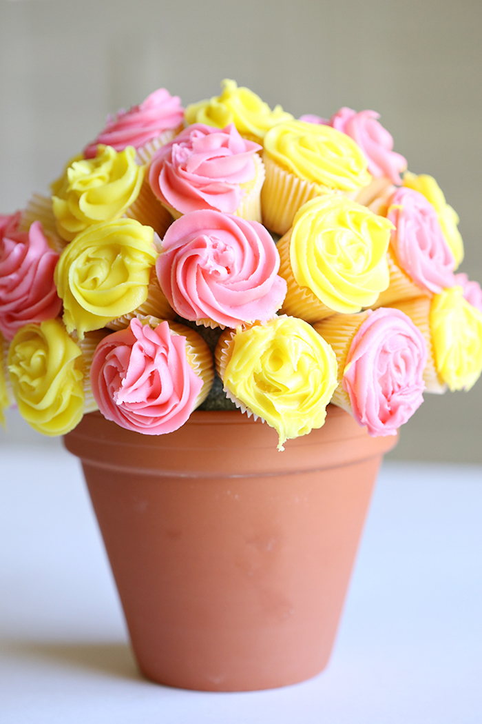 bouquet made from cupcakes, in yellow and pink, top 10 mother's day gift ideas, placed inside ceramic pot, in brownish-orange