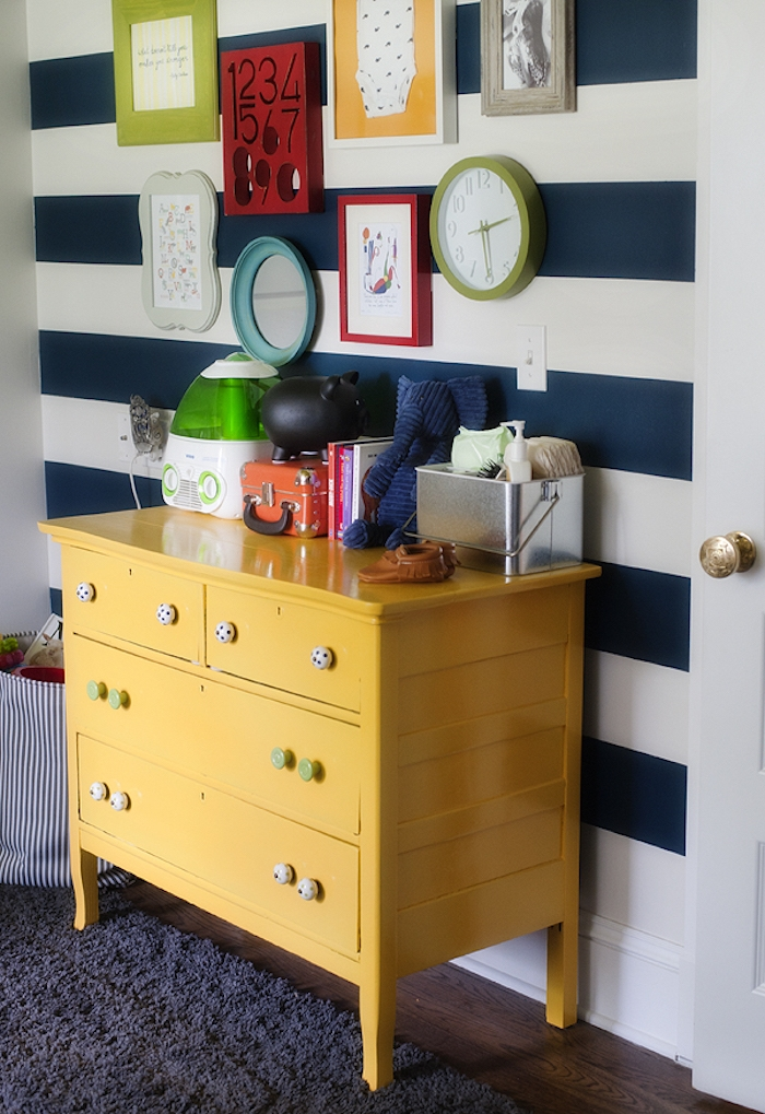 chest of drawers in bright yellow, covered with baby items and toys, nursery ideas, next to white wall, with navy stripes, decorated with images in colorful frames, mirror and a wall clock