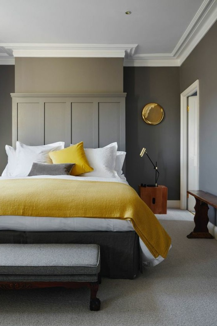 bench in dark brown, creamy grey bedroom with paneling, light gray carpet, bed with white and grey, and yellow covers and pillows