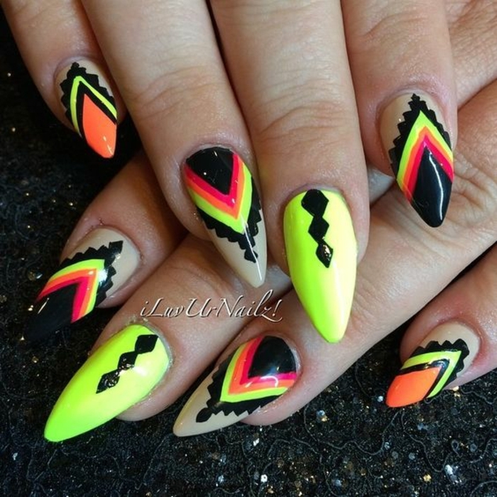 acid green or yellowish nail polish, decorated with black, red and orange hand-drawn elements, on oval pointy nails