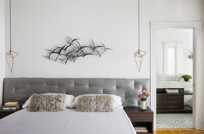 flock of black birds, 3D decoration mounted on a white wall, near modern hanging lamps, double bed with soft gray headboard, and two fluffy beige cushions