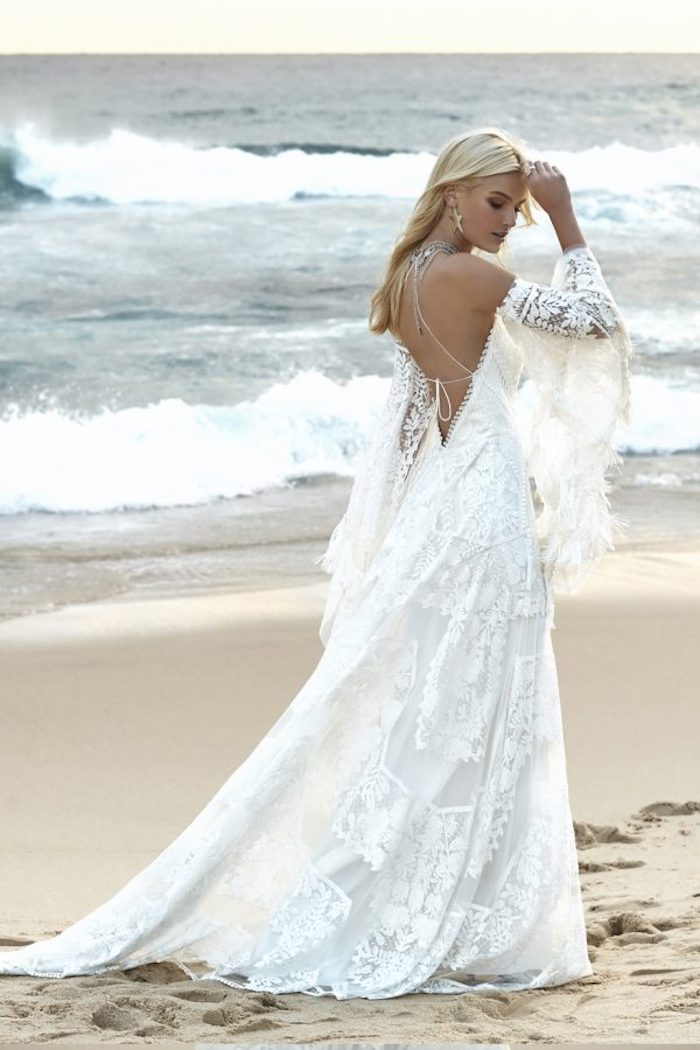 boho lace beach wedding dress, in white with wide tasseled sleeves, and a cutout back, worn by blonde woman, walking on a sandy shore