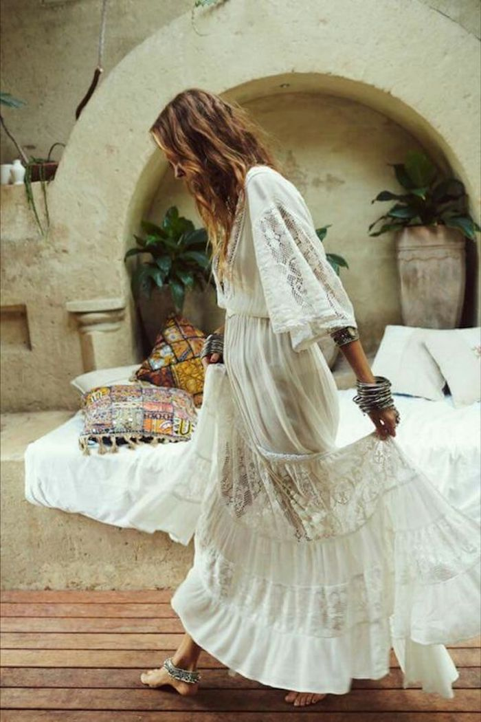 stonewall with arch and an inbuilt bench, covered with a white blanket and multi-colored cushions, and decorated with green potted plants, woman in boho maxi dress, with lace and embroidery, walking barefoot while holding her skirt