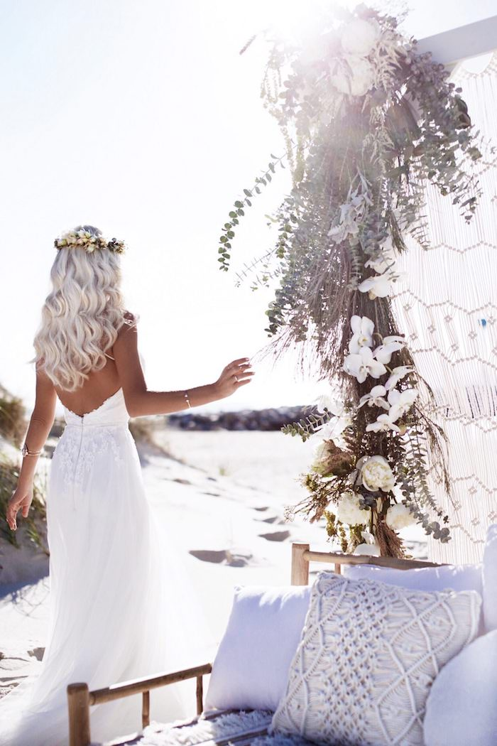 flower crown on a platinum blonde, curled long hair, worn by tanned slim woman, in a backless white gown, wedding dresses for beach wedding, settee with cushions and flowers nearby