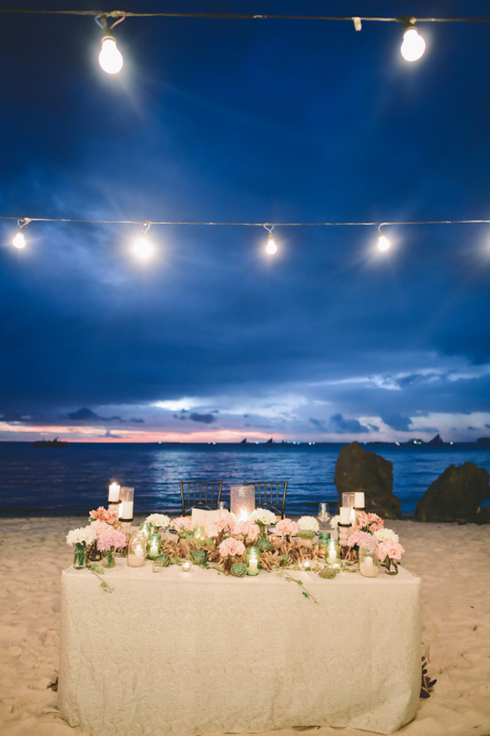 evening wedding near the sea, lavishly decorated table, with lots of flowers, florida destination weddings, string lights and candles