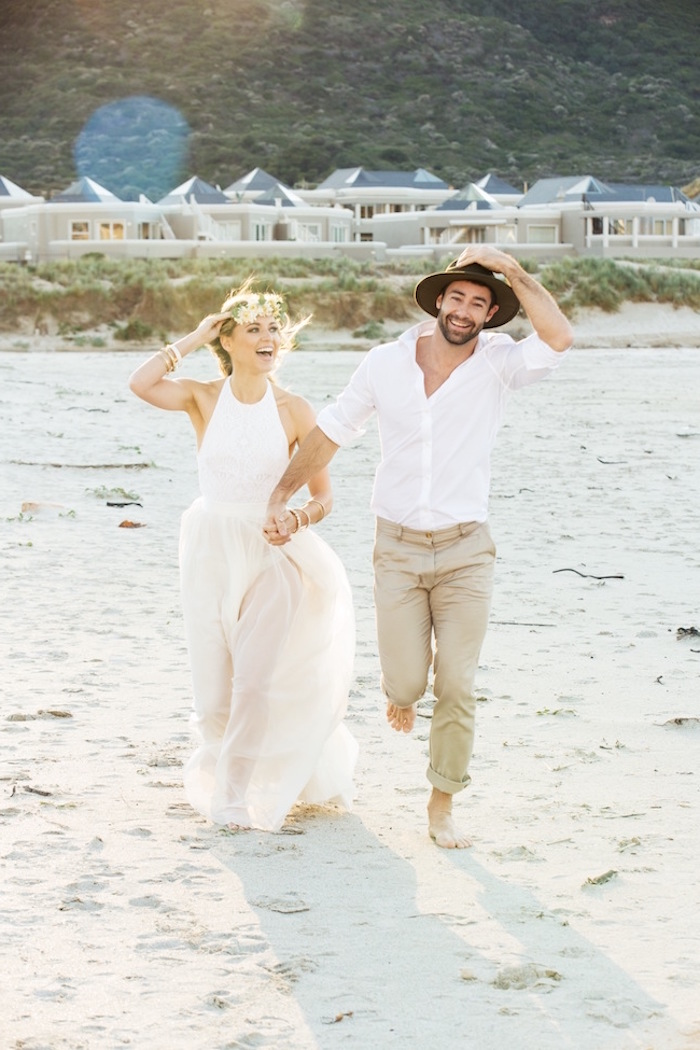semi-sheer white sleeveless gown, casual beach wedding dresses, worn by laughing blonde bride, with flower crown, running on a beach, hand in hand with a groom, in white shirt, beige pants and a hat